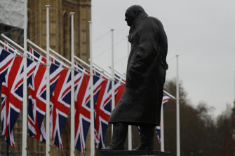 Union Jack flags hang outside Parliament near a statue of former prime minister Winston Churchill.