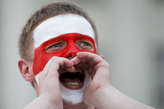 A man with a face painted with the old Belarusian national flag, shouts during opposition rally in front of the government building of Minsk.