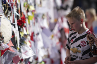 A boy looks at the messages left on the wall in Manchester.