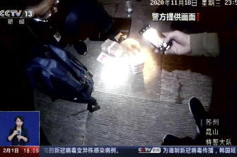 Policemen seize cash in China's Jiangsu Province in 2020, where police have arrested more than 80 suspected members of a criminal group that was manufacturing and selling fake COVID-19 vaccines, including to other countries.