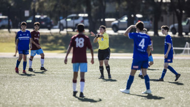 A young referee oversees a soccer match between Hakoah Sydney City East and APIA Leichhardt Tigers at Hensley Athletic Field in Eastlakes.