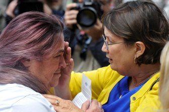 An emotional Tina Gasmi is comforted by Leonie Sheedy outside the royal commission into child sexual abuse in 2013.
