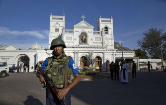 Sri Lankan military and clergy stand outside St Anthony's Shrine a day after the Easter Sunday attacks.