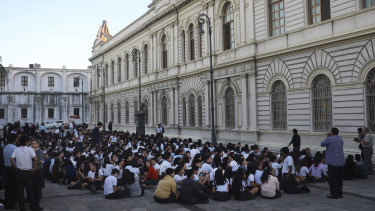 Students from a public school sit in an open area after being evacuated, in Veracruz, Mexico last year.
