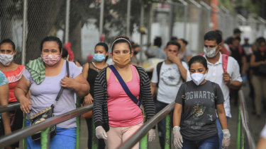 Workers wear masks as a protection against the spread of the new coronavirus as they leave from a day's work in Managua.