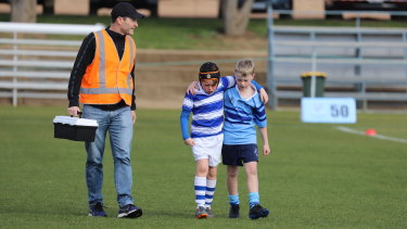 'In a world full of Covid – be kind': Brody Grainger, 9, a player for St Edmund's College being comforted by Marist opponent Theo Campton, 10, at a weekend junior rugby game last weekend in Canberra, with Dr Michael Koppman also helping out.