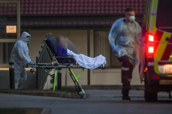 A patient leaves St Basil's Homes for the Aged in Fawkner last month during an outbreak at the facility.