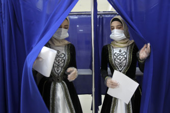 Chechen women in traditional dress leave a polling booth in Grozny, Russia, on Sunday.