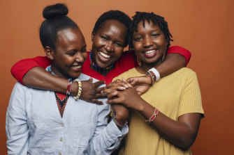 Dr Kakenya Ntaiya, in red, is the first Maasai woman to go to university in the US, pictured with two university students Peyian Kortom (in yellow) and Sharon Tiyo (blue).