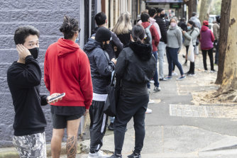 People outside a Sydney Centrelink office in July after lockdowns hit the city. UNSW research shows many will take a hit to their finances as assistance is cut by the federal government.