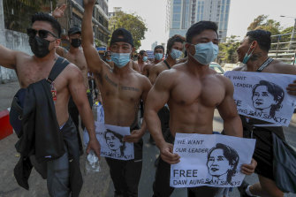 A group of shirtless demonstrator hold images of ousted Myanmar leader Aung San Suu Kyi during a protest in Yangon, Myanmar, on Wednesday.
