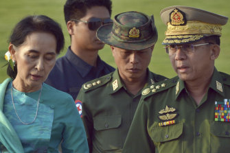 Aung San Suu Kyi (left) who has been detained in the coup, walks with General Min Aung Hlaing (right) in 2016.