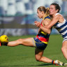 Grounded: Crow Nikki Gore is caught as she attempts to kick away against the Cats at GMHBA Stadium on Sunday.