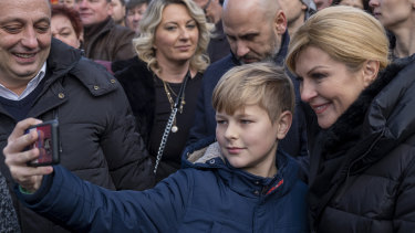 A boy takes a selfie with the Croatian President Kolinda Grabar Kitarovic, right, at a rally near Zagreb on New Year's Eve.