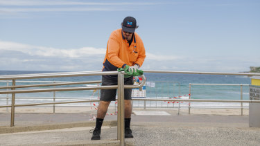 A Waverley Council worker cleans a railing at Bondi beach. While some council employees are busier than ever, others have been stood down because of coronavirus.