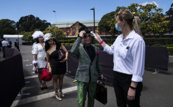 Melbourne Cup Day attendees at Randwick Racecourse having their temperature checked on entry.