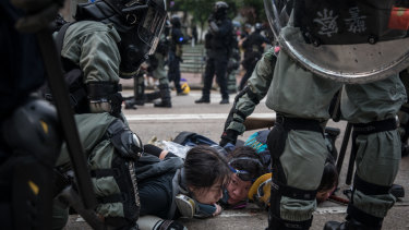 Pro-democracy protesters are arrested by police during clashes after a march in Hong Kong.