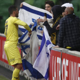 Tomer Hemed of the Phoenix wraps himself in the flag of Israel to celebrate a goal from a penalty during the A-League match between Melbourne City and the Wellington Phoenix.
