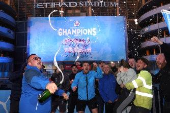 Manchester City fans celebrate the Premier League title outside Etihad Stadium.