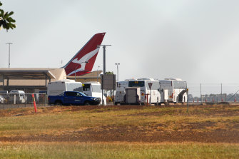 Buses wait to transport passengers from flight QF112 to Howard Springs.