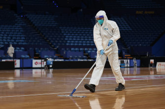 A staff member in PPE cleans the court following the round five Super Netball match between the Fever and the Giants.