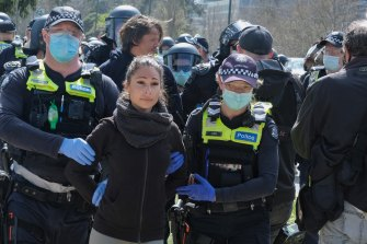 A woman is led from the protest by police.