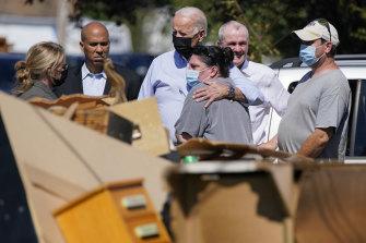President Joe Biden hugs a person as he tours a neighbourhood impacted by Hurricane Ida.