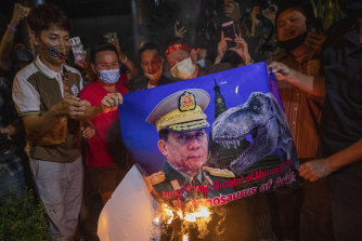 Myanmar nationals living in Thailand set fire to a picture of military leader Min Aung Hlaing during a protest in front of Myanmar embassy in Bangkok.