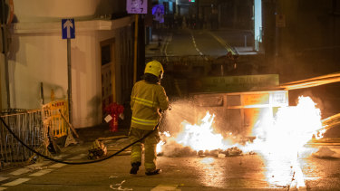 A firefighter extinguishes a fire set by demonstrators during a protest in Sheung Wan district of Hong Kong.