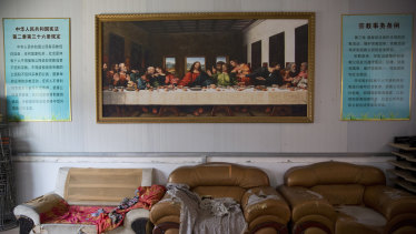 A painting of the Last Supper next to posters quoting China's constitution on religious freedom in a house church shut down by authorities near the city of Nanyang in central China's Henan province.