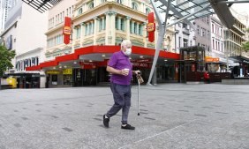 A lone man walks in an otherwise empty Queen Street Mall in Brisbane's CBD on Saturday.