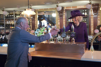 Camilla, the Duchess of Cornwall, serves Prince Charles a pint at one of Poundbury's two pubs.