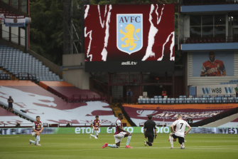 Players kneel before the start of the English Premier League soccer match between Aston Villa and Sheffield United on Wednesday.