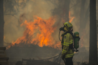 Firefighter Adam Brown protects properties along Glenthorne Road in South Taree on Sunday.