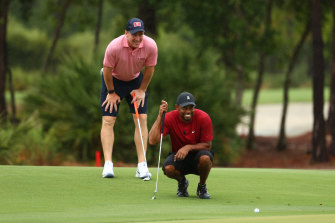 Peyton Manning gives his playing partner Tiger Woods some tips during their match-up against Tom Brady and Phil Mickelson in Florida.