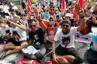 Pro-democracy activists gesture with a three-fingers salute, a symbol of resistance, as they arrive at the Attorney-General's office in Bangkok, in March.
