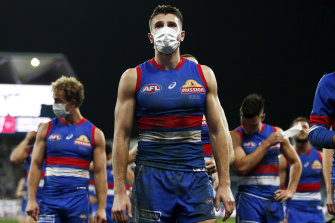 A masked Marcus Bontempelli leads the Bulldogs off the ground after the loss to the Cats.