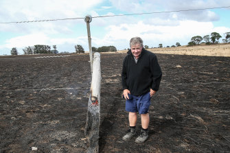 Jack Kenna inspects a burnt-out power pole on his property at The Sisters.