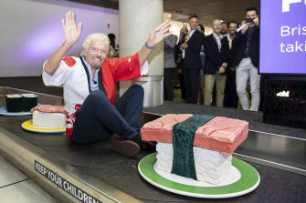 Sir Richard Branson, founder of Virgin Group arrives on a giant sushi train. Brisbane Tokyo flights announcements at Brisbane Airport