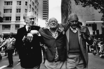 Tom Jones (left) and Henry McLachlan (right) help Norm Glover make it the end of the Anzac Day march in Sydney in 1991.