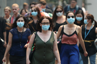 People are seen wearing face masks to protect from smoke haze as they cross a busy street in Sydney's CBD on Thursday.