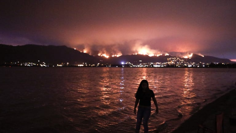 A girl wades through water while watching a wildfire burn in the Cleveland National Forest in Lake Elsinore, California.