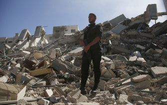 A policeman stands on the rubble of the media building destroyed by an Israeli airstrike.
