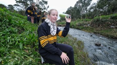 It's not rubbish: Eve Zimmermann, 11, throws a water bottle into Dandenong Creek to track where litter goes.