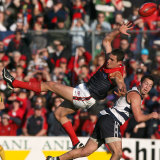 Brad Miller in the air as Geelong's Jimmy Bartel goes by.