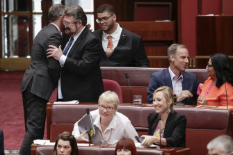 Greens leader Richard Di Natale and Senator Derryn Hinch embrace after the Senate agreed on amendments to  a bill in the Senate in February.