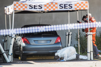 Homicide squad detectives and forensic officers examine a car at the Mernda police station.