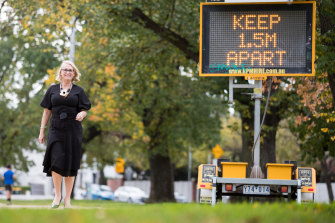 Melbourne lord mayor Sally Capp next to a sign urging social distancing.