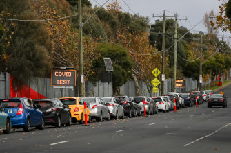 Cars line up outside a drive through COVID-19 testing facility at the Melbourne Showgrounds.
