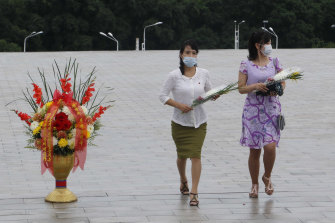 People visit the statues of former North Korean leaders Kim Il-sung and Kim Jong-il to lay flowers.